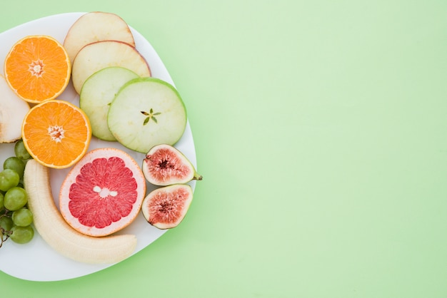 Peeled banana; grapes; orange; grapefruit; fig and slices of apple and pear fruit on white plate over the mint green backdrop Free Photo