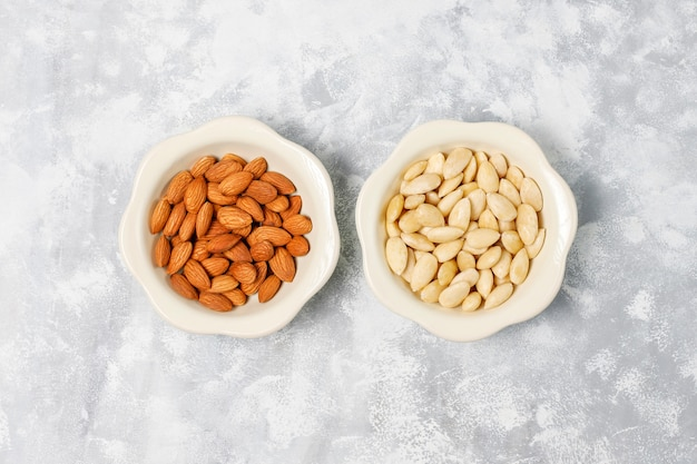 Peeled (blanched) and unblanched whole almonds in ceramic bowls on grey concrete Free Photo