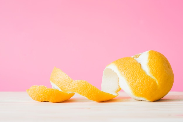 Peeled orange fruit in front of pink wall Free Photo