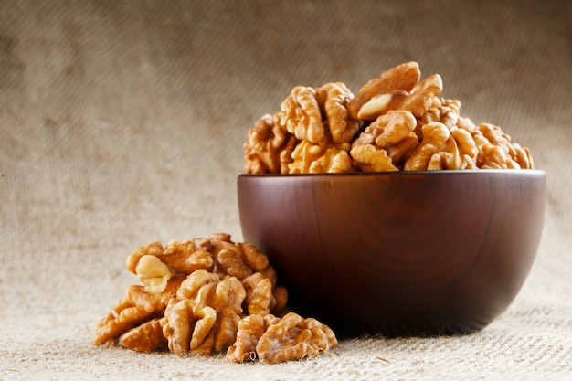 Peeled walnuts in a wooden, dark brown cup on a burlap cloth Premium Photo