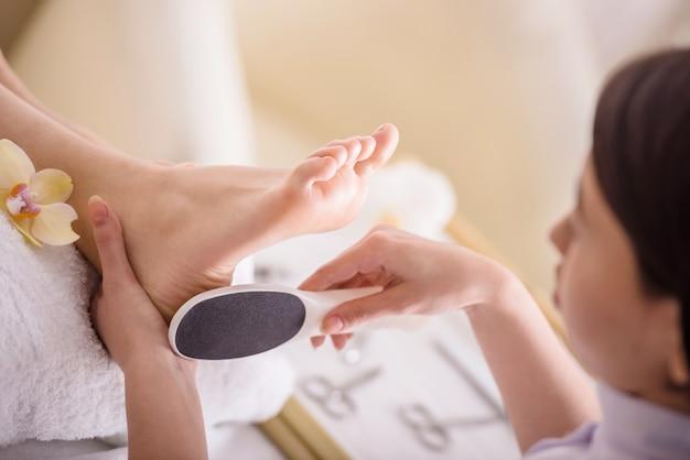 Peeling feet pedicure procedure in a beauty salon. Premium Photo