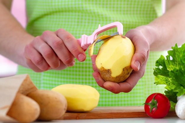 Premium Photo | Peeling ripe potato using a peeler for cooking fresh  vegetable dishes in kitchen at home.