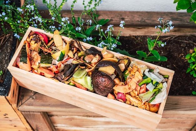 自家製の堆肥を作るための木枠の皮と有機性廃棄物。 Premium写真
