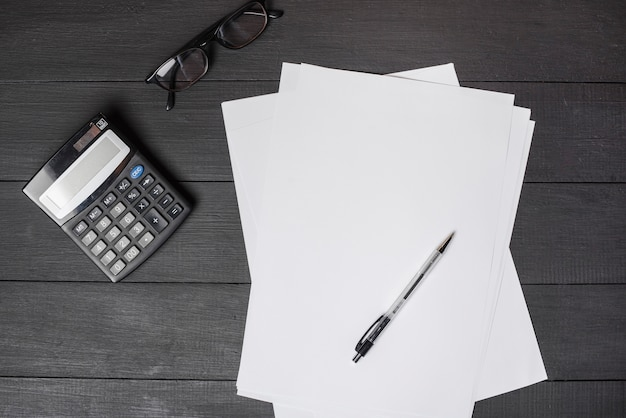 Pen on blank white papers; calculator and eyeglasses on black wooden table Free Photo