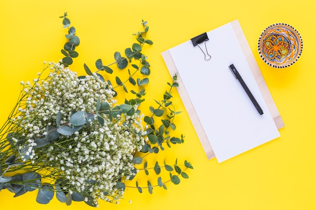 Pen on clipboard; colorful bowl and baby's breath flowers on yellow backdrop Free Photo