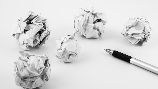 Pen and crumpled paper ball on a white table. - work and business ideas concept. Premium Photo