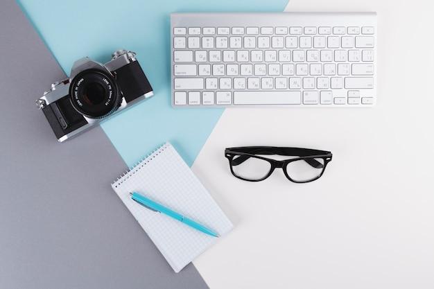 Pen near notebook, camera, eyeglasses and keyboard Free Photo