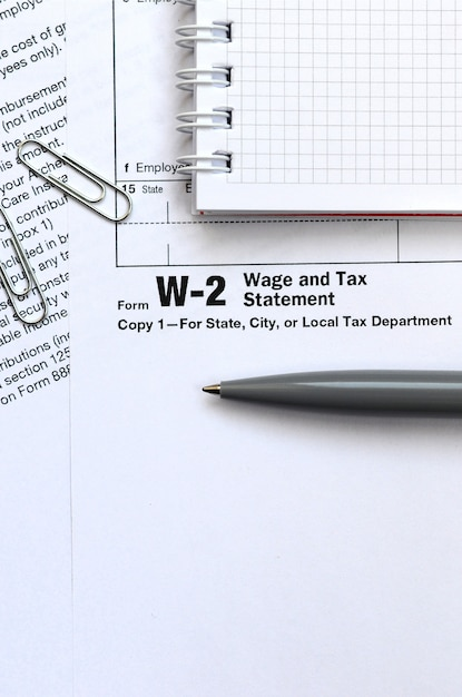 The pen and notebook on the tax form w-2 wage and tax statement. the time to pay taxes Premium Photo