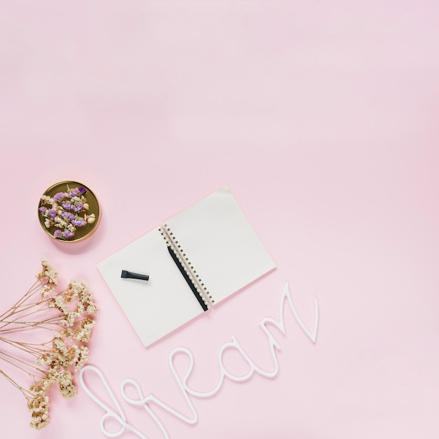 Pen on spiral notebook with flowers and dream text on pink background Free Photo