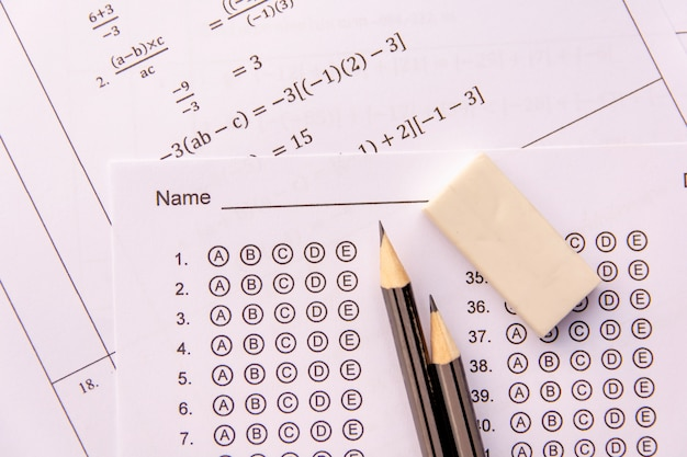 Pencil and eraser on answer sheets or standardized test form with answers bubbled. Premium Photo