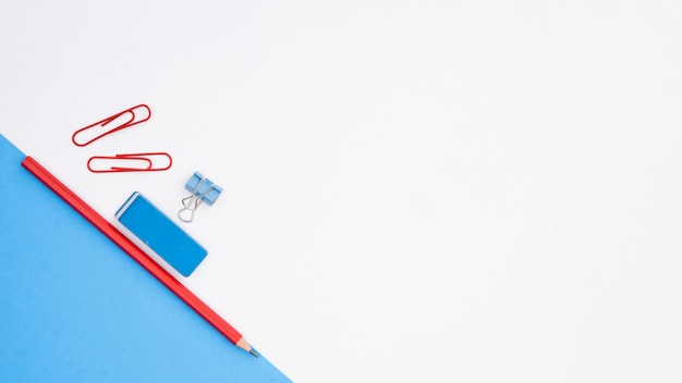 Pencil; eraser and paper clip with blue card paper on white backdrop Free Photo