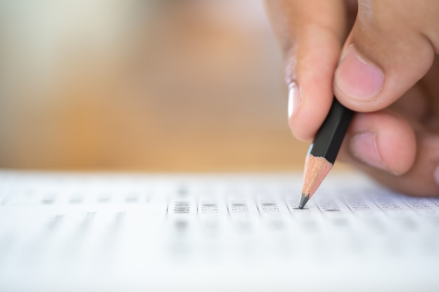 Pencil on hand writing answer of question test examination Premium Photo