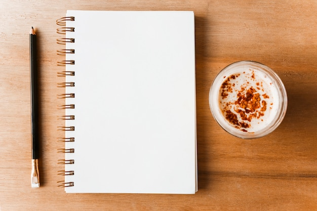 Pencil; spiral blank notepad and coffee on wooden backdrop Free Photo