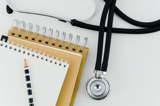Pencil on the stack of spiral notepad with stethoscope on white backdrop Free Photo