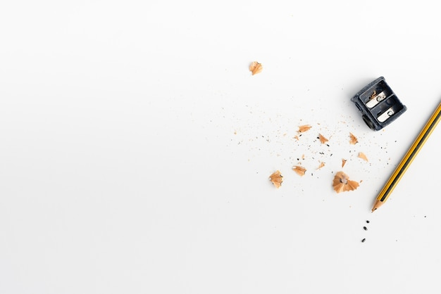 Pencil with pencil sharpener and wood shavings on white backdrop Premium Photo