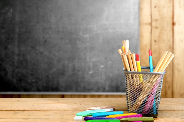 Pencils in basket container and colorful crayons on the wooden table with blackboard Premium Photo