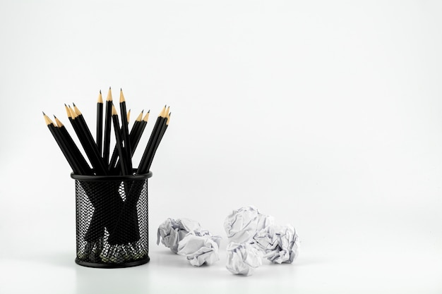Pencils in basket and crumpled paper ball on a white table Premium Photo