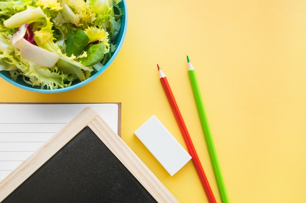 Pencils and rubber near blackboard and salad Free Photo