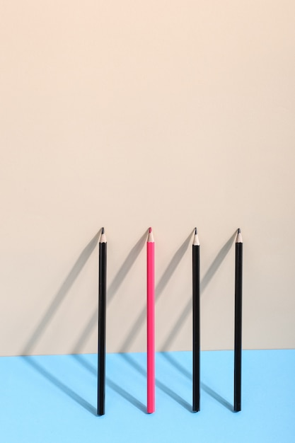 Pencils stand against the wall, casting a shadow, drawing geometric shapes. Premium Photo