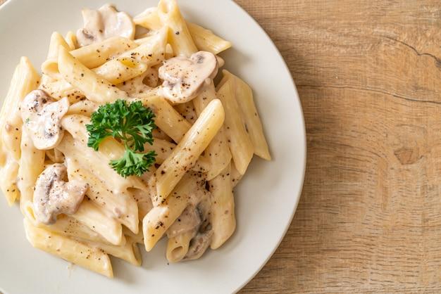キノコのペンネパスタカルボナーラクリームソース、イタリア料理のスタイル Premium写真