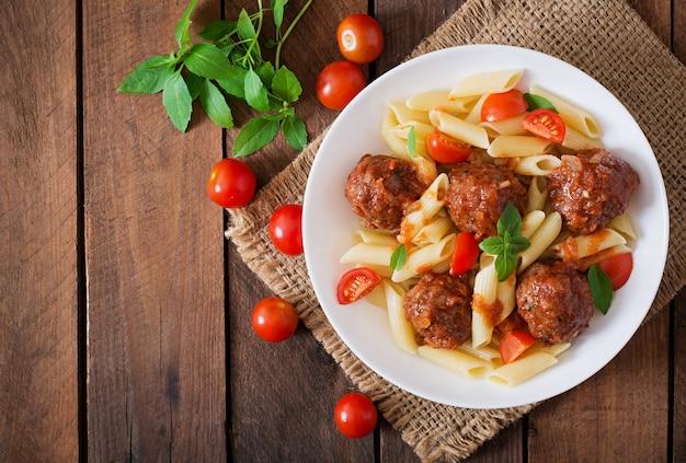 Паста пенне с фрикадельками в томатном соусе в белой миске Бесплатные Фотографии
