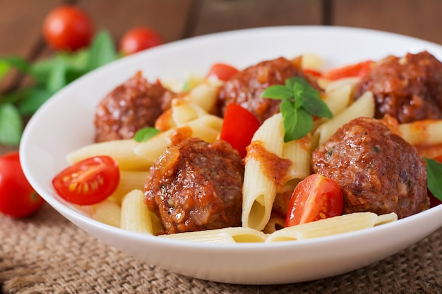 Penne pasta with meatballs in tomato sauce in a white bowl Free Photo