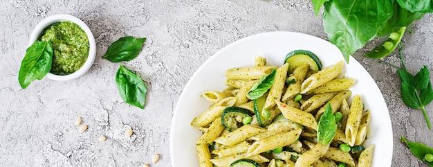 Паста с соусом песто, цуккини, зеленым горошком и базиликом. итальянская еда. вид сверху. плоская планировка Бесплатные Фотографии