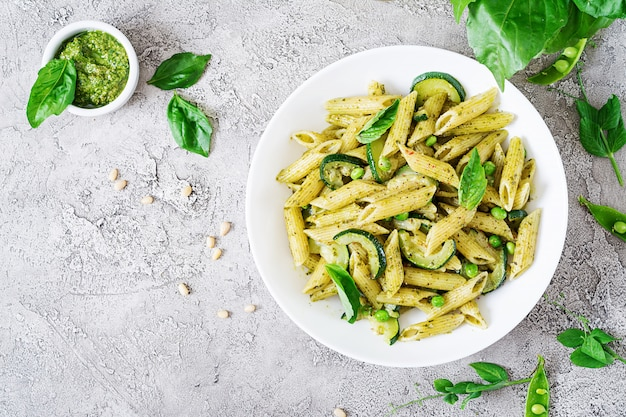 Penne pasta with  pesto sauce, zucchini, green peas and basil. italian food. top view. flat lay. Free Photo