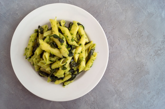 Penne pasta with spinach on grey background. Premium Photo