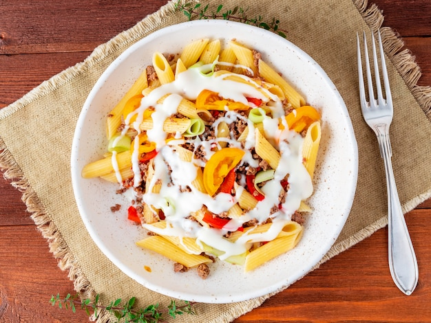 Penne pasta with yellow tomatoes, vegetables, mincemeat, white sauce Premium Photo