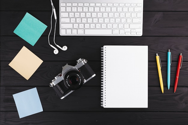 Pens near notebook, camera, earphones, papers and keyboard Free Photo
