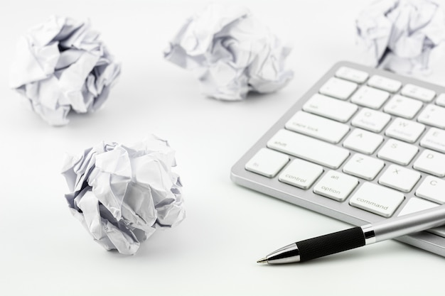 Pens placed on computer keyboard and wrinkled paper balls on a white table Premium Photo