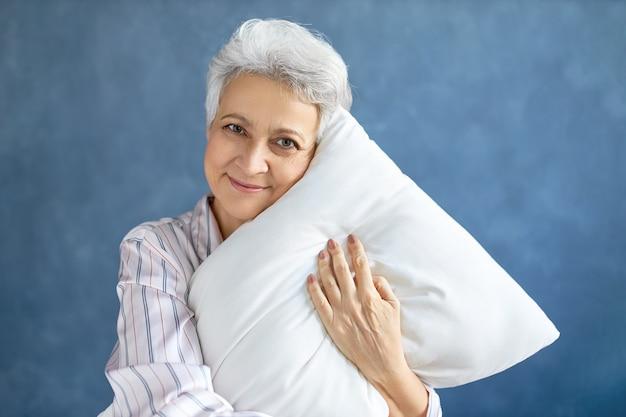 Пенсионерка позирует и обнимает белую мягкую подушку Бесплатные Фотографии