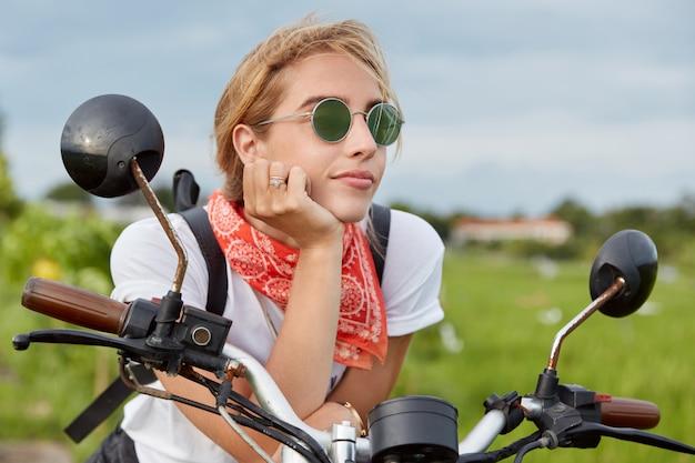 物思いにふけるアクティブな女性は、バイクに座っている間、思慮深い表情で遠くを見て、長い運転の後に休憩し、屋外の輸送でポーズし、高速で素晴らしい自然を楽しんでいます 無料写真