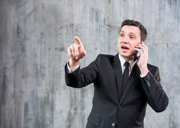 Pensive adult businessman speaking on phone Free Photo