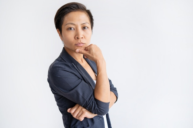 Pensive asian business woman touching chin with fingers Free Photo