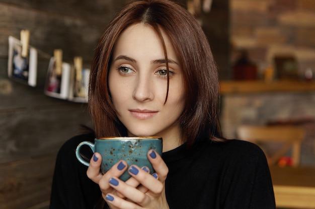 Задумчивая привлекательная молодая европейка с коричневыми шоколадными волосами в элегантном черном платье держит чашку капучино, мечтает, наслаждаясь горячим и свежим напитком, сидя в уютной кофейне Бесплатные Фотографии