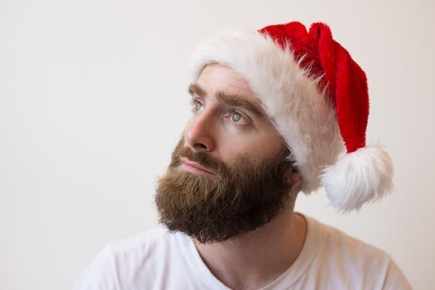Pensive bearded man wearing santa hat Free Photo