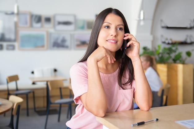 잠겨있는 아름 다운 젊은 여자 셀에 얘기, 공동 작업에 서, 책상에 기대어, 멀리보고 웃 고 무료 사진