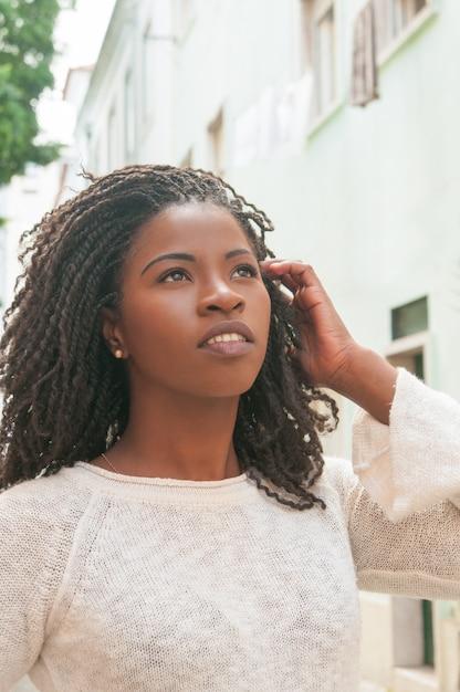 Pensive black girl walking down city alley Free Photo