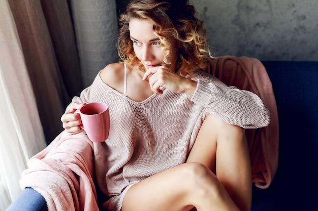 ピンクのニットの居心地の良いラウンジで物思いにふけるブロンドの女性は、お茶を飲みます。朝早く。ホーム。 無料写真