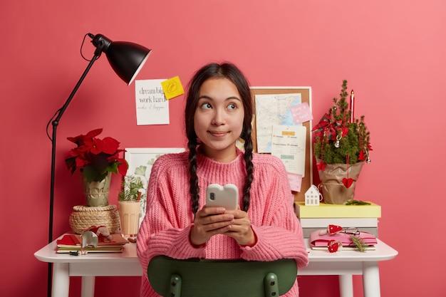 Ragazza adolescente bruna pensierosa legge il messaggio di notizie nei social network, controlla l'equilibrio, si siede su una sedia contro il desktop accogliente con albero di abete decorato, zabaione, taccuini, guadagna soldi online Foto Gratuite