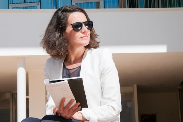 Pensive business lady reading her notes Free Photo