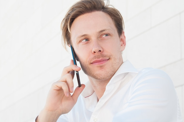 Pensive business man calling on smartphone outdoors Free Photo