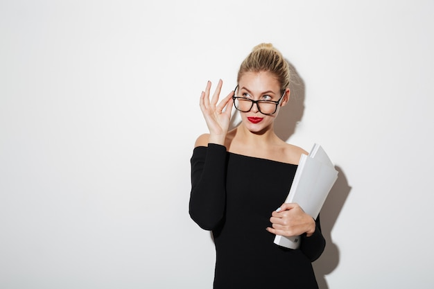 Pensive business woman in dress and eyeglasses holding documents Free Photo