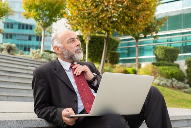 Pensive businessman using laptop on steps Free Photo