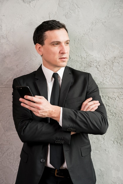 Pensive businessman with crossed arms looking away Free Photo