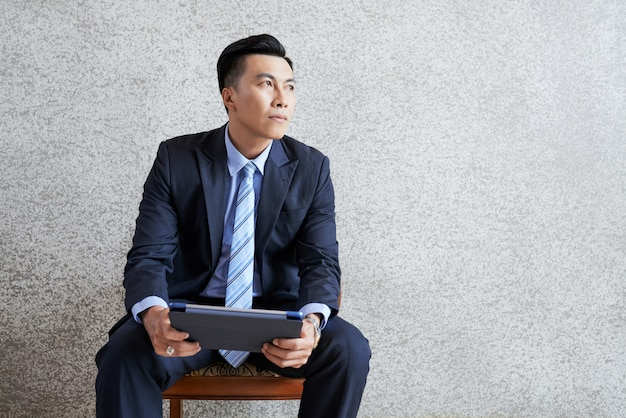 Pensive businessman with tablet Free Photo