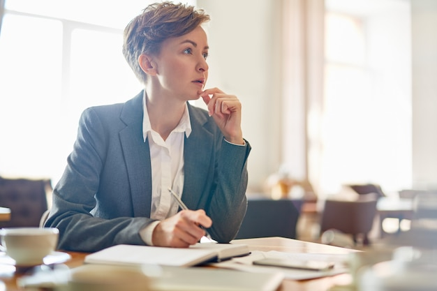Pensive businesswoman at coffeehouse Free Photo