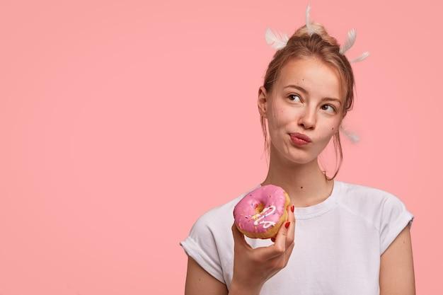 Donna caucasica pensierosa con le piume sulla testa, guarda pensierosamente da parte, tiene una deliziosa ciambella dolce, vestita con una maglietta bianca casual, sta contro il muro rosa con uno spazio vuoto per il testo Foto Gratuite